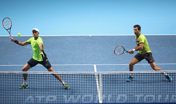 Horia Tecau strikes a forehand shot with partner Jean-Julien Rojer looking on (Photo: Clive Brunskill/Getty Images)