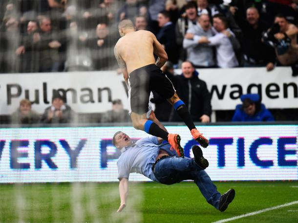 A celebrating Mitrovic jumps over pitch invading fan | Photo: FCExclusive.com
