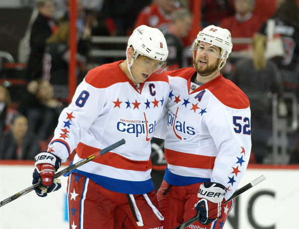 Mike Green #52 congratulates teammate Alexander Ovechkin #8 of the Washington Capitals after Ovechkin scored his 400th career goal on an empty net in the third period agianst the Carolina Hurricanes during their game at PNC Arena on December 20, 2013 in Raleigh, North Carolina. The Capitals won 4-2. (Dec. 19, 2013 - Source: Grant Halverson/Getty Images North America)