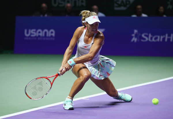 Angelique Kerber bends down to hit a backhand against Dominika Cibulkova during the final of the 2016 BNP Paribas WTA Finals Singapore presented by SC Global. | Photo: Clive Brunskill/Getty Images