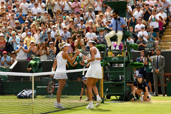 Angelique Kerber and Garbine Muguruza meet at the net for a warm handshake after their encounter | Photo: Shaun Botterill/Getty Images Europe