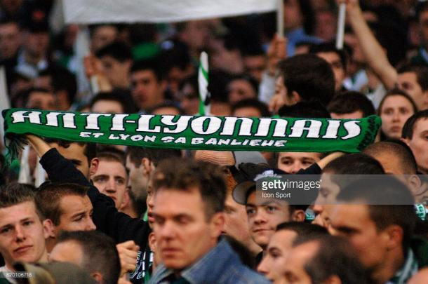 A Saint-Etienne supporter holds aloft an anti-Lyon scarf. Source | Getty Images.