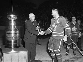 George Armstrong (right) shakes hands with commissioner Clarence Campbell after captaining the Maple Leafs to their third consecutive Stanley Cup in 1964. Armstrong, never the star player of the Leafs, captained Toronto to its last four Stanley Cups in the 1960s. Photo: Hockey Hall of Fame