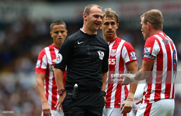 Madley prepares to issue a yellow card. Source | Getty Images.