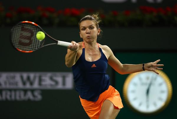 Simona Halep returns a serve | Photo: Clive Brunskill/Getty Images North America