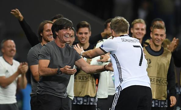 Schweinsteiger celebrates with his manager. | Image credit: PATRIK STOLLARZ/AFP/Getty Images