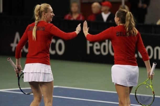 Govortsova and Sasnovich high-five after winning a point in their doubles match. Photo: Fed Cup