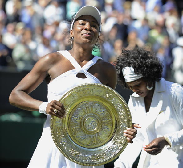 Venus Williams smiles for the cameras after beating sister Serena, seen behind her, to win the Wimbledon title ine 2008 (Getty/Bloomberg)