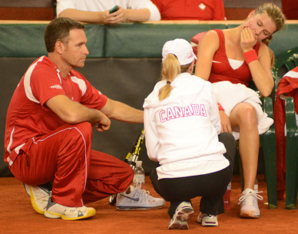 Eugenie Bouchard (right, seated) gets treatment during the 2013 Fed Cup playoffs. Photo: Fed Cup
