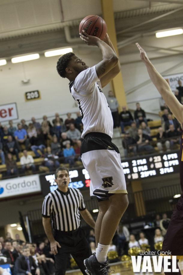 Reggie Jones (23) takes the three point shot with a defender in his face. Photo: Walter Cronk