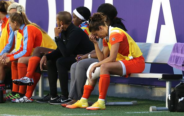 Carli Lloyd #10 of Houston Dash sits on the bench with ice on her knee during a NWSL soccer match against the Orlando Pride at the Orlando Citrus Bowl on April 23, 2016 in Orlando, Florida | Alex Menendez - Getty Images