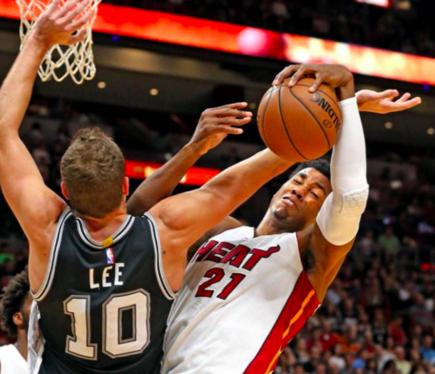 Hassan Whiteside (21) gets tangled with Spurs forward David Lee (Charles Trainor Jr./Miami Herald)