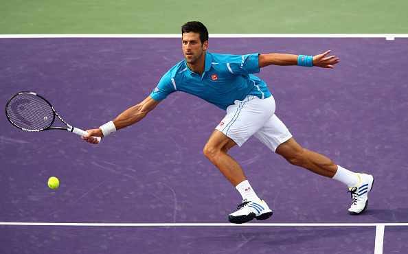 Djokovic rushes to the net to hit the volley. Credit: Clive Brunskill/Getty Images