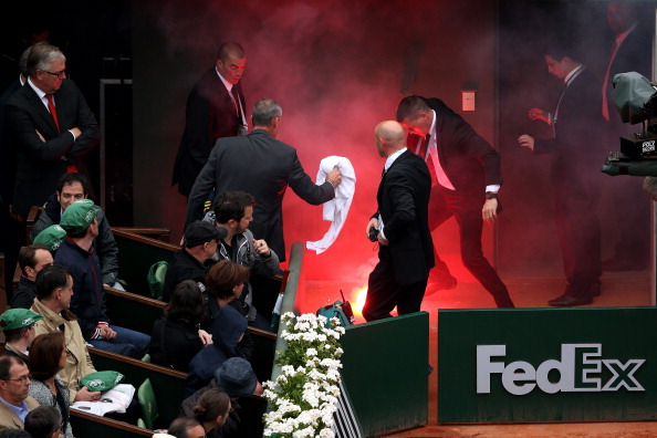 Security guards put-out the flare that a fan was able to run onto the court during the 2013 men's final between Nadal and Ferrer. Credit: Clive Brunskill/Getty Images