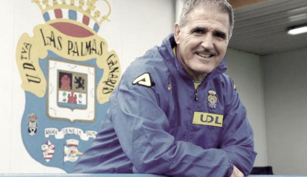 Paco Herrera delante de lescudo de la UD Las Palmas | Foto: www.compartirpasion.com
