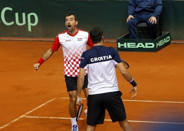 Ivan Dodig (facing) and Marin Cilic celebrate their comeback victory. Photo: Predrag Milosavljevic/Davis Cup