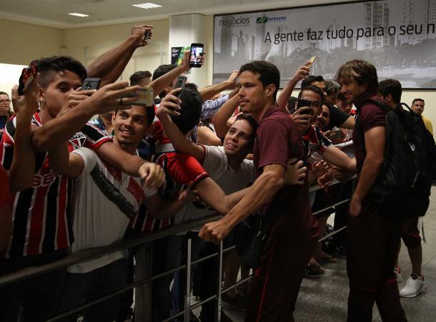 Hernanes e Lugano no desembarque da delegação no aeroporto de Goiana Divulgação: Twitter Oficial do São Paulo Futebol Clube
