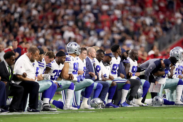 Members of the Dallas Cowboys link arms and kneel during the National Anthem before the start of the NFL game against the Arizona Cardinals. (Sept. 24, 2017 - Source: Christian Petersen/Getty Images North America)