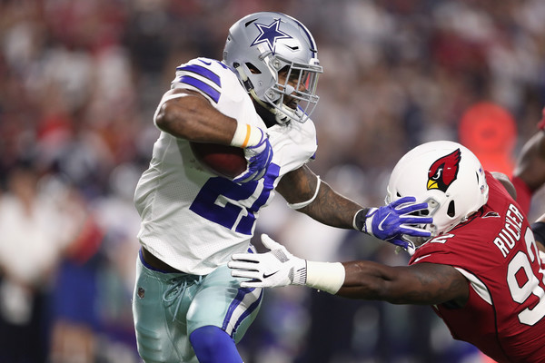 Running back Ezekiel Elliott #21 of the Dallas Cowboys stiff arms defensive end Frostee Rucker #92 of the Arizona Cardinals. (Sept. 24, 2017 - Source: Christian Petersen/Getty Images North America)