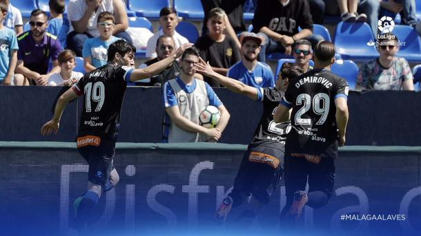 Manu celebra con sus compañeros el primer tanto, ante la mirada de asombro de los aficionados. Fuente: LaLiga
