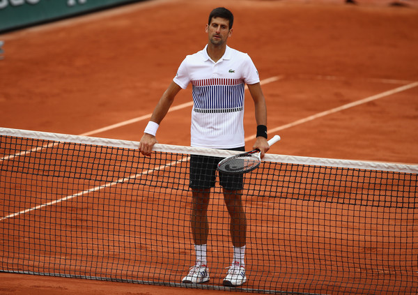 Djokovic waits alone at the net after his quarterfinal loss at the French Open, where he was the defending champion and had reached three straight finals. Photo: Clive Brunskill/Getty Images