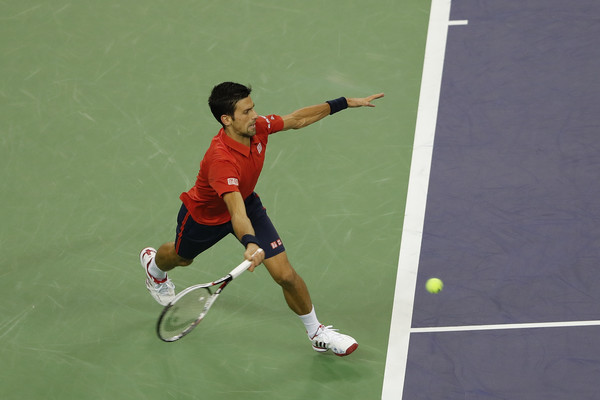 Novak Djokovic chases down a forehand during his semifinal loss. Photo: Lintao Zhang/Getty Images