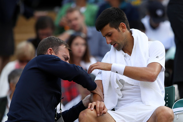 Djokovic receives treatment on his elbow during the Wimbledon quarterfinal. Photo: Julian Finney/Getty Images