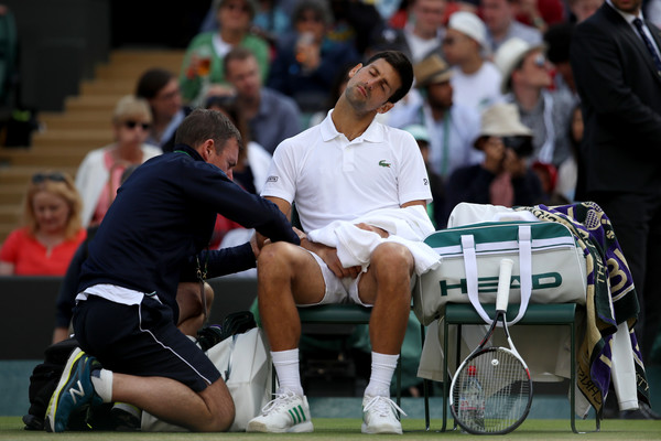 Novak Djokovic receives medical treatment on his elbow during the Wimbledon quarterfinals. Photo: Julian Finney/Getty Images