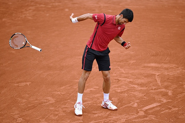 Djokovic flings his racquet in frustration, nearly hitting a linesman. Photo: Martin Bureau/AFP/Getty Images
