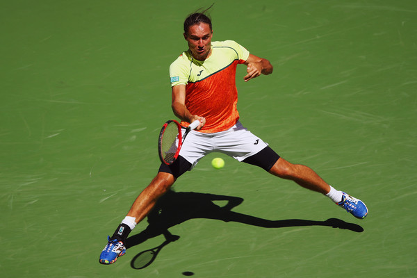 Alexandr Dolgopolov slides into a forehand during his fourth-round loss. Photo: Clive Brunskill/Getty Images