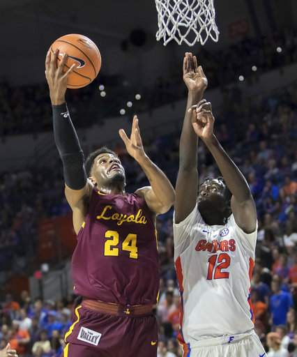 Loyola's Aundre Jackson shoots a layup over Florida's Gorjok Gak during the Ramblers' win/Photo: Ron Irby/Getty Images