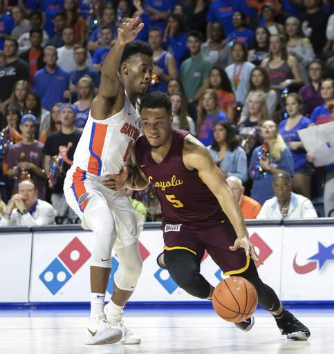 Loyola's Marques Townes drives past Florida's Mark Okauru during Wednesday night's game/Photo: Ron Irby/Associated Press