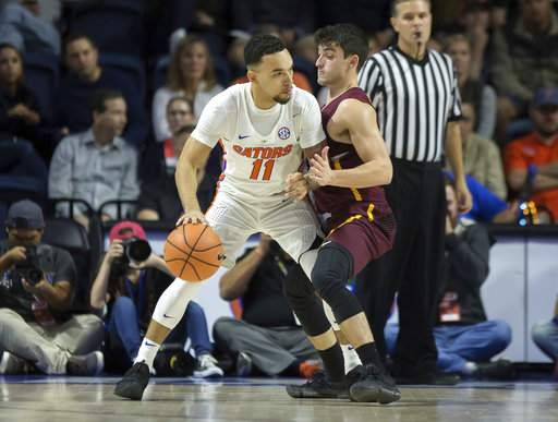 Chris Chiozza of Florida tries to drive against Loyola's Clayton Custer during last night's game in Gainesville/Photo: Ron Irby/Associated Press