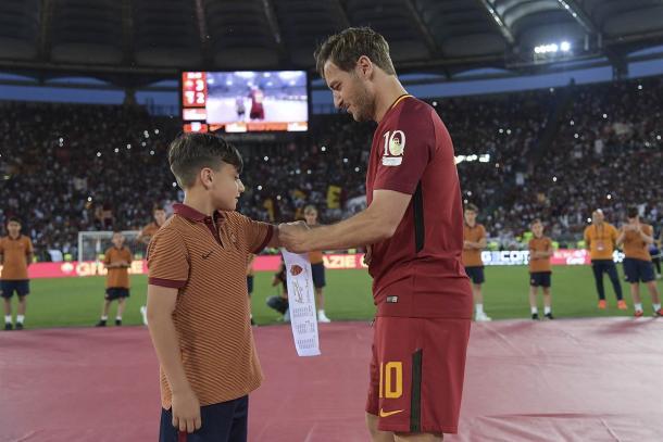 Totti,en su homenaje, entrega su brazalete al capitán más joven de las inferiores romanas. / Imagen web AS Roma.