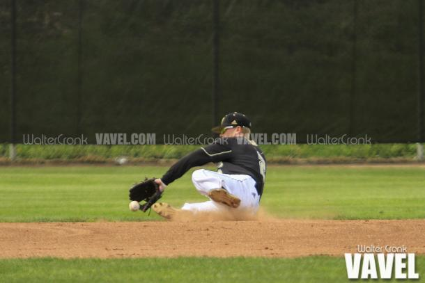 Connor Smith (2) makes the sliding stop at shortstop. Photo: Walter Cronk