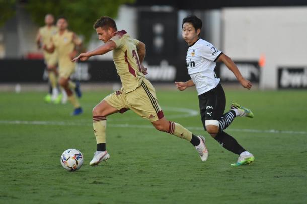 Cayarga controlando el balón perseguido por Kang-in Lee