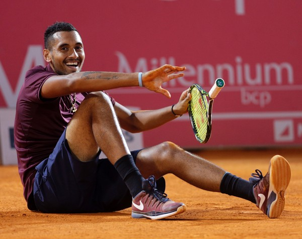 Australian Nick Kyrgios laughs after falling on the pitch playing against Croatian Borna Coric during their quarter-final Estoril Open Tennis tournament in Estoril on April 29, 2016. / AFP / JOSE MANUEL RIBEIRO