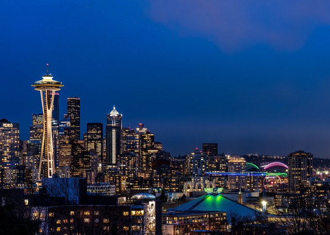 Vista del Skyline de Seattle con el Climate Pledge Arena iluminado en la parte inferior derecha