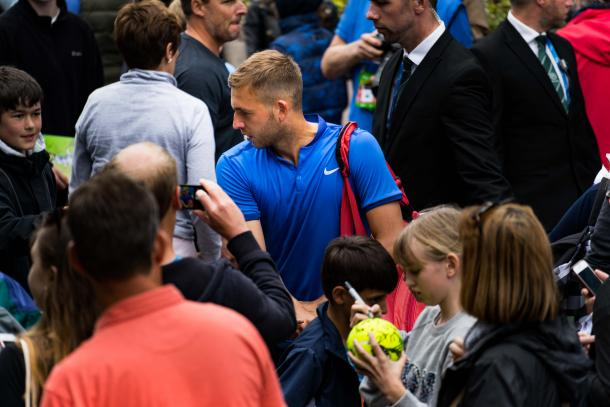 Evans celebrates victory as he signs autographs for the fans. Photo: LTA