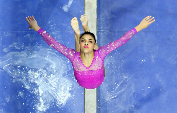 Laurie Hernandez performing a difficult balance beam skill. Photo Credit: Ezra Shaw of Getty Images