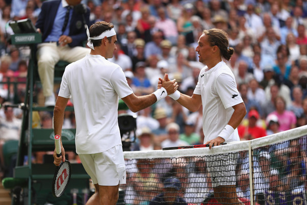 Federer (left) and Dolgopolov shake hands as the Ukrainian retires. Photo: Michael Steele/Getty Images