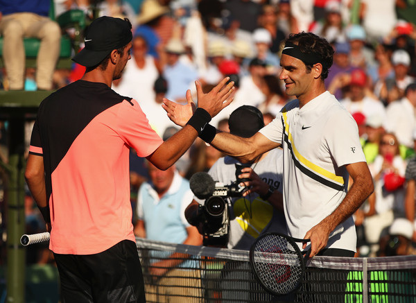 Federer (right) shakes hands with Kokkinakis after their wild second round match. Photo: Clive Brunskill/Getty Images