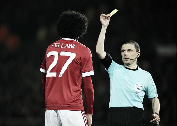 Marouane Fellaini in familiar pose, receiving a yellow card against Liverpool (Photo: Matthew Ashton / Getty Images)