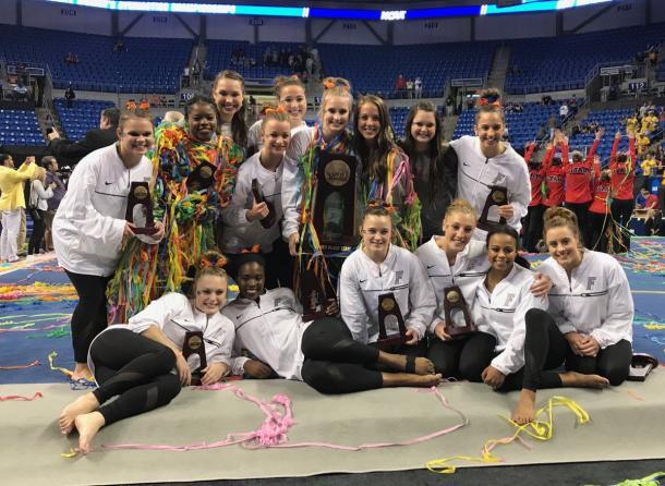 Florida celebrates the third place trophy. Photo Credit: Florida Gators Gymnastics Twitter.
