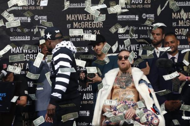 Mayweather threw money over McGregor in one of the more theatrical moments of their New York press conference (image: USA Today)