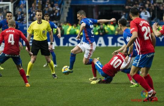 El colegiado cántabro, López Toca, sigue de cerca un lance del juego entre Rocha y Carmona en el derbi asturiano. | Imagen: La Liga