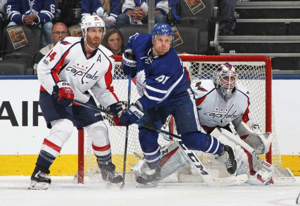 Brooks Orpil (left) and Leo Komarov (in blue) battle in front of Holtby. Photo: Claus Andersen/Getty Images