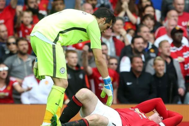 Bravo looks on worryingly as Rooney is hurt after his tackle in the box | Photo: Getty