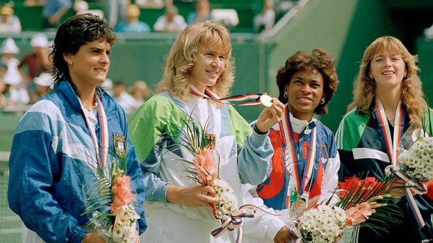 Graf (second from the left) holds up her Olympic Gold Medal after beating Sabatini (left) in the final. Photo: AP/Lionel Cironneau
