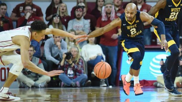 Carter knocks the ball away from Oklahoma's Jamuni McNeace during West Virginia's victory in Norman/Photo: Kyle Phillips/Associated Press